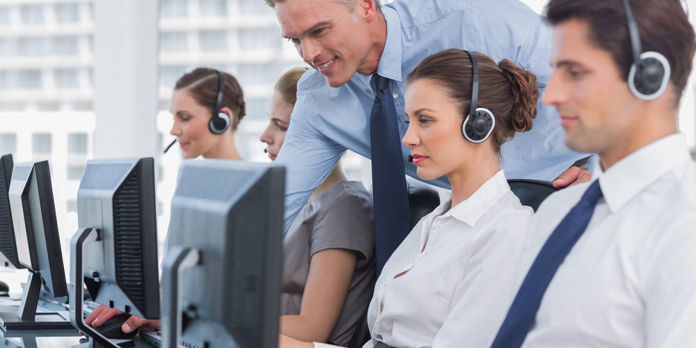 Smiling manager helping call centre agent with a headset